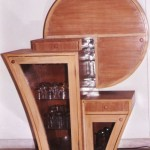 This flip down bar made for the first home of Kamaths in 1997 holds up to 10 bottles and 3 dozen glasses. There are 2 drawers for accessories too. The budget was flexible and this small unit become the highlight of the living room.